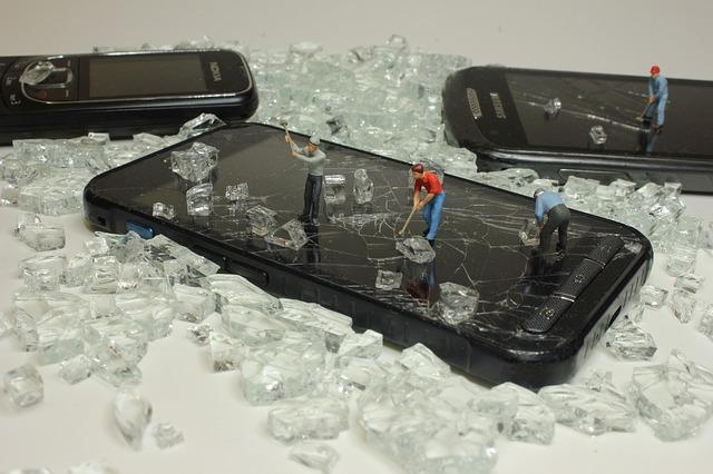 rozbitý displej na telefonu – malé figurky, které ho rozbíjejí
